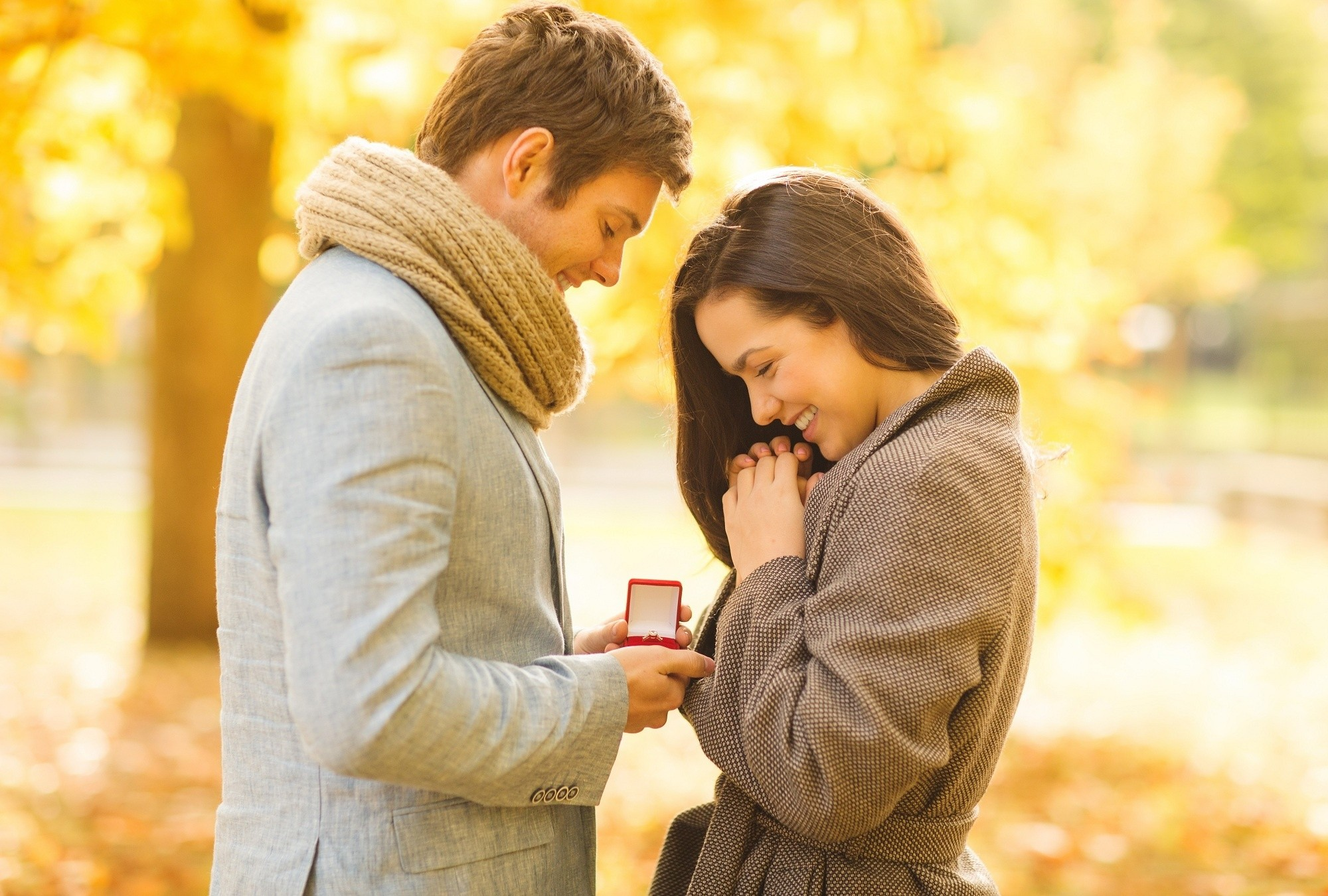 engagement ring, love proposal, holidays, love, couple, relationship and dating concept - romantic man proposing to a woman in the autumn park